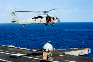 An MH-60R Seahawk helicopter places cargo onto the flight deの写真素材 [FYI02690621]