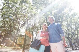 ショッピングを楽しむ外国人カップルと陽光の写真素材 [FYI02690990]