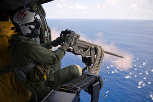 Naval Aircrewman fires a .50-caliber machine gun from a MH-6の写真素材 [FYI02691547]