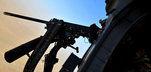 Soldier mans the .50 caliber machine gun on a HH-60G Pave Haの写真素材 [FYI02691665]