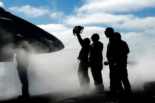 A flight deck crew member shows the pilot of an F/A-18 Horneの写真素材 [FYI02691700]