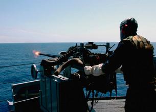 U.S. Navy Gunner's Mate fires a Mark 38 (MK-38) 25 mm machinの写真素材 [FYI02691776]
