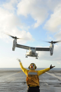 Aviation Boatswain's Mate signals an MV-22 Osprey to land.の写真素材 [FYI02691878]