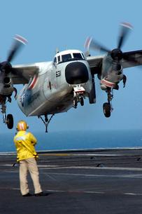 A U.S. Navy officer observes a C-2A Greyhound aircraft landiの写真素材 [FYI02691894]