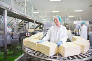 Worker with large blocks of cheese at production line in processing plantの写真素材 [FYI02691905]