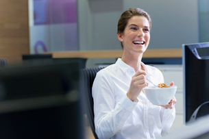 Happy businesswoman eating cereal at desk in officeの写真素材 [FYI02691925]