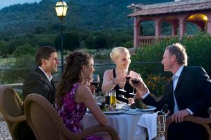 Well-dressed couples toasting wine glasses on restaurant balconyの写真素材 [FYI02691941]