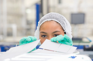 Technician worker arranging solar cells to form solar panel on production lineの写真素材 [FYI02691943]