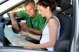 Mature couple looking at map in car, man with disposable cup, smilingの写真素材 [FYI02691950]