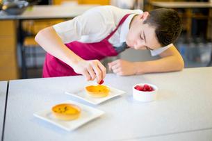 Focused male high school student plating dessert in home economics classの写真素材 [FYI02691980]