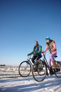 Father and daughter riding bicycles together on winter dayの写真素材 [FYI02691988]