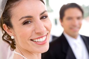 Bride and groom posing at wedding, focus on bride, smiling, close-up, portraitの写真素材 [FYI02691994]