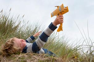 Boy Playing With Model Aeroplane On Beachの写真素材 [FYI02691995]