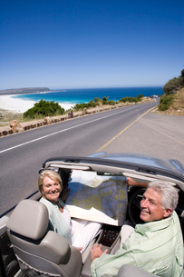 South Africa, Cape Town, senior couple with map parked on side of road by sea in convertible silverの写真素材 [FYI02691998]