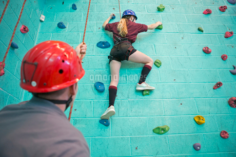 High school student holding rope supporting classmate climbing rock climbing wallの写真素材 [FYI02692022]