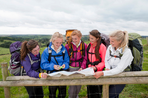 Girls with backpacks looking down at compass and map against fence in fieldの写真素材 [FYI02692023]