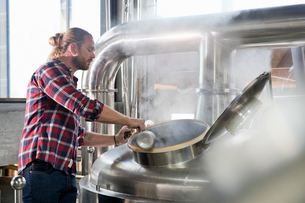 Male Brewery Worker Checking Fermentation Process In Steel Vatの写真素材 [FYI02692030]
