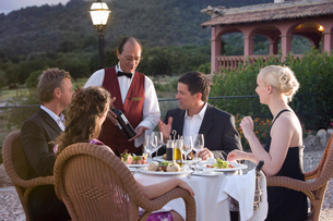 Waiter presenting wine bottle to well-dressed couples at table on restaurant balconyの写真素材 [FYI02692031]