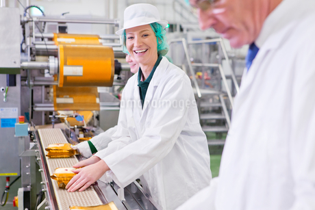 Portrait smiling worker stacking cheese on production line in processing plantの写真素材 [FYI02692054]