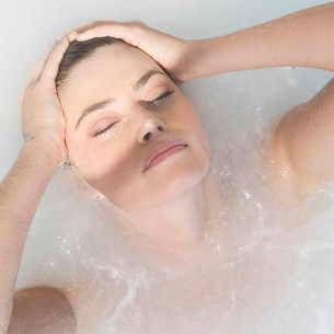 A woman relaxing in a hot tubの写真素材 [FYI02692055]