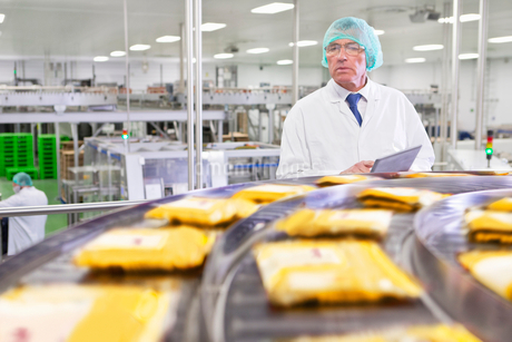 Quality control worker with digital tablet watching cheese at production line in processing plantの写真素材 [FYI02692075]