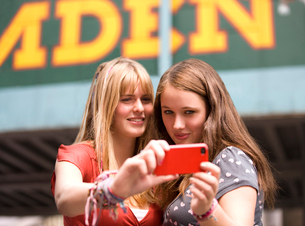 Two teenage girls taking a photograph of themselves in Camdeの写真素材 [FYI02692082]
