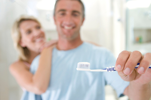 Woman embracing man holding up toothbrush, smiling, portrait (focus on toothbrush)の写真素材 [FYI02692085]