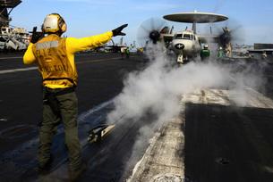 Aviation Boatswain's Mate directs an E-2C Hawkeye on the fliの写真素材 [FYI02692103]