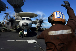 A Sailor signals to pilots of an E-2C Hawkeye aboard USS Johの写真素材 [FYI02692115]