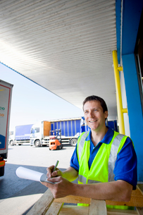 Worker writing on clipboard on loading dockの写真素材 [FYI02692140]