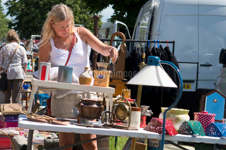 Woman Browsing On Stall At Outdoor Flea Marketの写真素材 [FYI02692151]