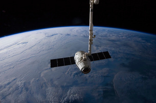 The SpaceX Dragon cargo craft is suspended in the grasp of tの写真素材 [FYI02692171]