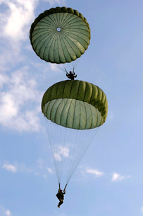 U.S. Army Soldiers parachute down after jumping from a C-130の写真素材 [FYI02692172]