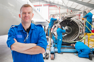 Team Of Aero Engineers Working On Aircraft In Hangarの写真素材 [FYI02692191]