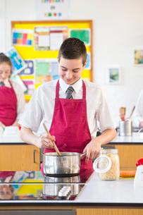 Male high school student cooking in home economics classの写真素材 [FYI02692196]