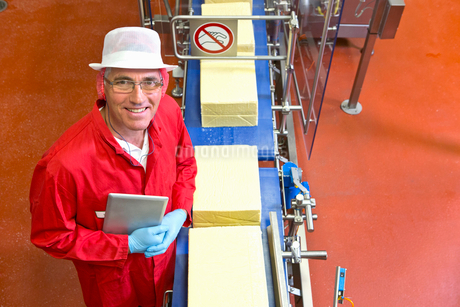 High angle view portrait of smiling quality control worker with digital tablet at production line inの写真素材 [FYI02692231]