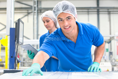 Technician worker smiling at camera arranging solar cells to form solar panel on production lineの写真素材 [FYI02692234]