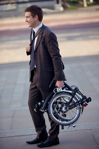 A businessman carrying his folded bicycle to workの写真素材 [FYI02692272]