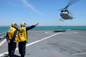 Airmen direct a Spanish navy AB-212 helicopter onto the fligの写真素材 [FYI02692307]