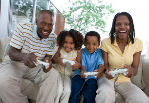 Two generation family playing video games console on sofa at home, smiling, front view (tilt)の写真素材 [FYI02692310]