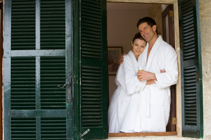 Couple in bathrobes hugging and looking out windowの写真素材 [FYI02692330]
