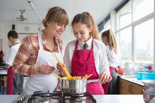 Home economics teacher teaching high school student pasta cookingの写真素材 [FYI02692364]