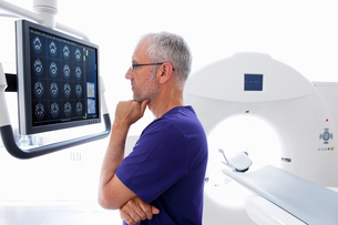 Serious doctor reviewing digital brain scan at CT scanner in hospitalの写真素材 [FYI02692367]