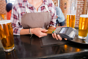 Waitress Processing Credit Card Payment In Barの写真素材 [FYI02692382]