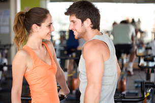 Man and woman smiling at each other in gym, side viewの写真素材 [FYI02692409]