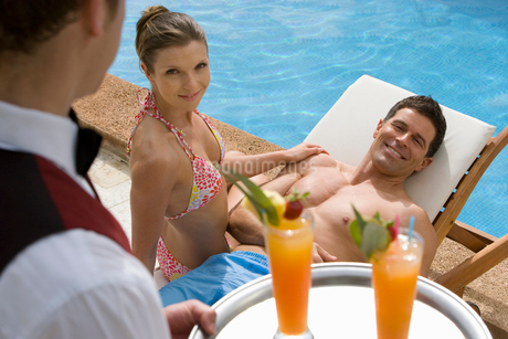 Waiter serving tropical drinks to couple sitting at poolsideの写真素材 [FYI02692413]