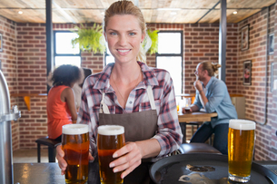 Portrait Of Waitress By Counter In Bar With Tray Of Drinksの写真素材 [FYI02692441]