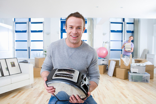 Smiling man holding toaster as woman unpacks in living roomの写真素材 [FYI02692452]