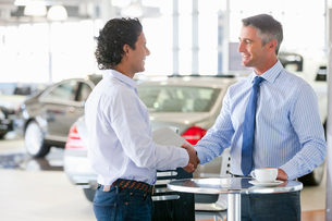 Salesman and customer shaking hands at table in car dealership showroomの写真素材 [FYI02692472]