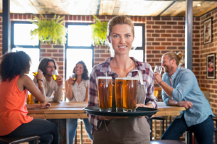 Portrait Of Waitress By Counter In Bar With Tray Of Drinksの写真素材 [FYI02692473]